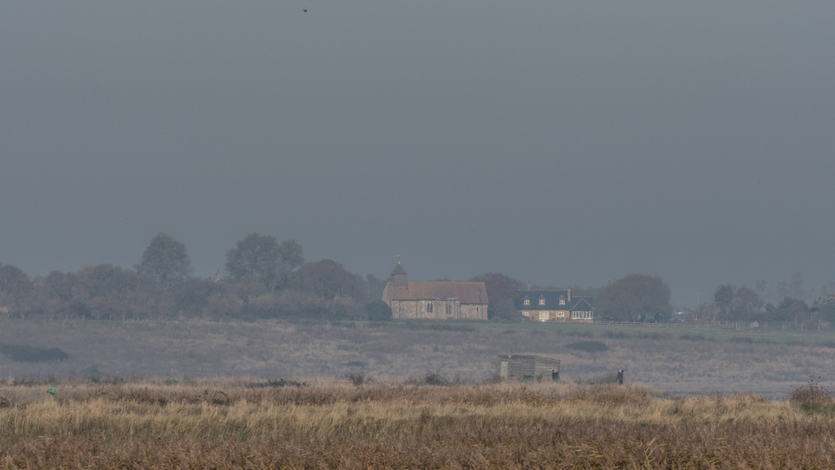 Birdwatchers on Oare Marshes - the early Norman church at Harty on the Isle of Sheppey behind